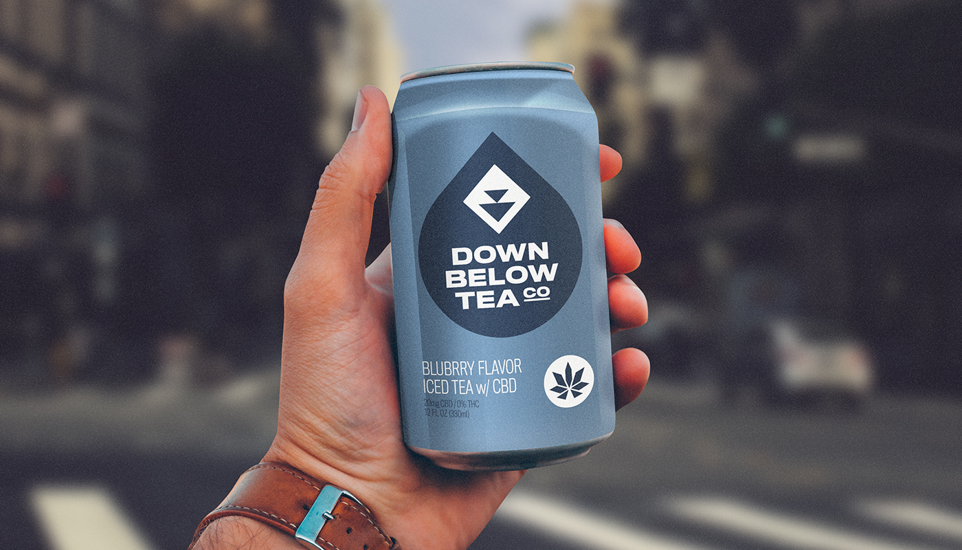 man holding down below tea co cbd iced tea can in hand on busy city street visual identity by connor fowler cfowlerdesign