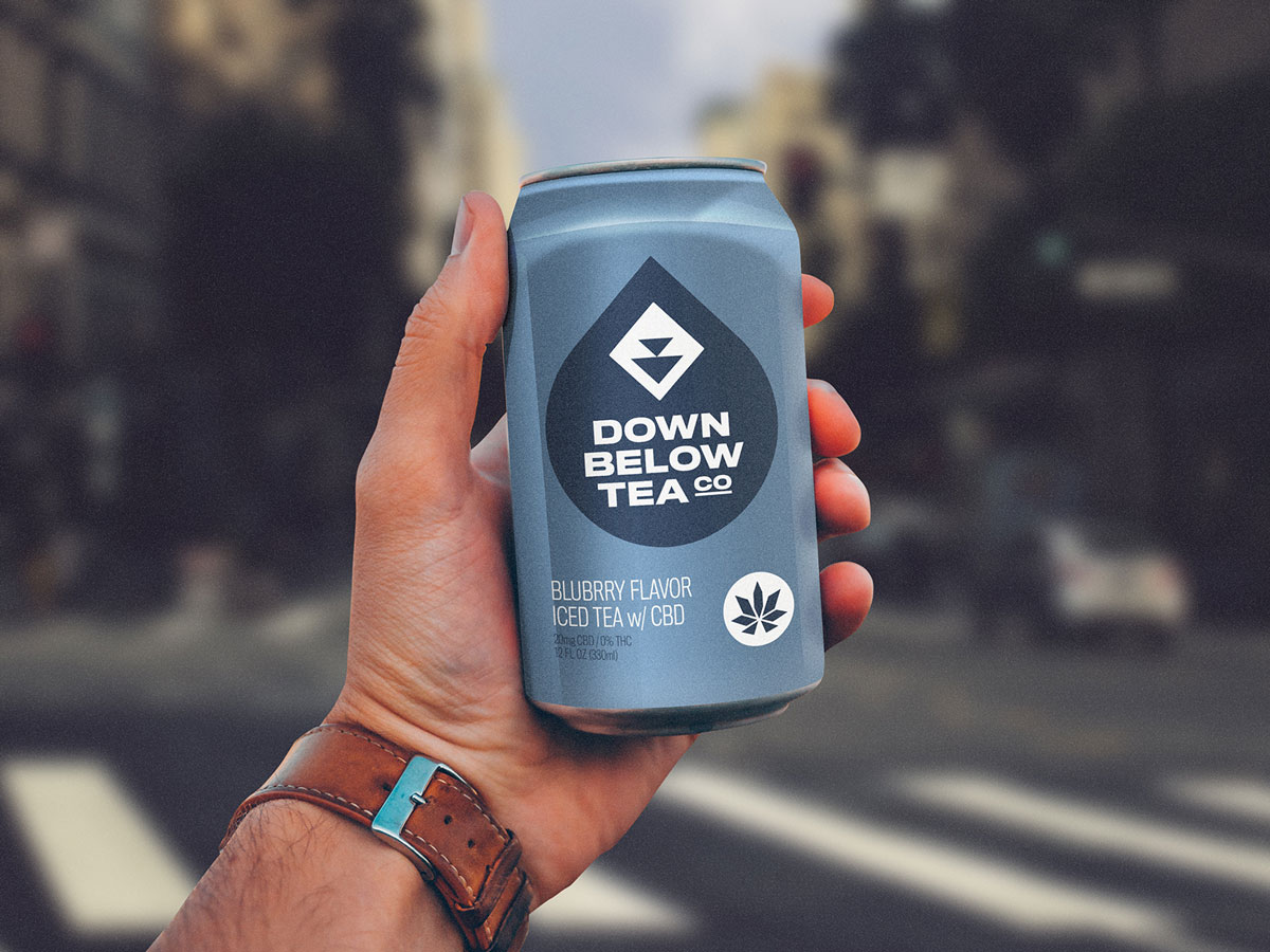 man holding down below tea co blueberry flavor cbd iced tea in hand on busy city street visual identity by connor fowler cfowlerdesign