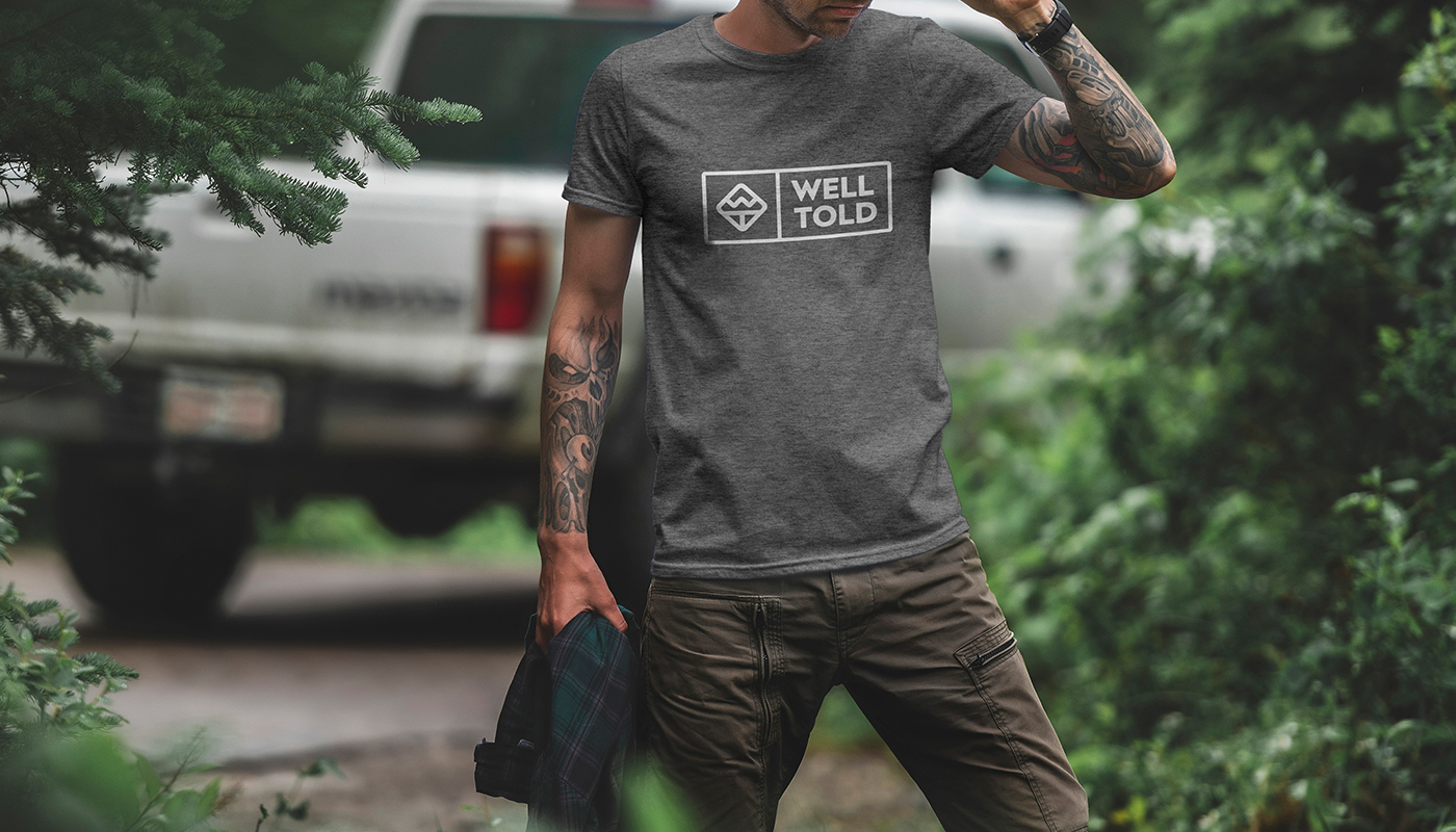 man wearing well told grey t-shirt in forest logo design badge branding well told business card design home goods brand logo design wt letter logowell told etched water bottle flasks map glassware logo design branding visual identity by connor fowler cfowlerdesign