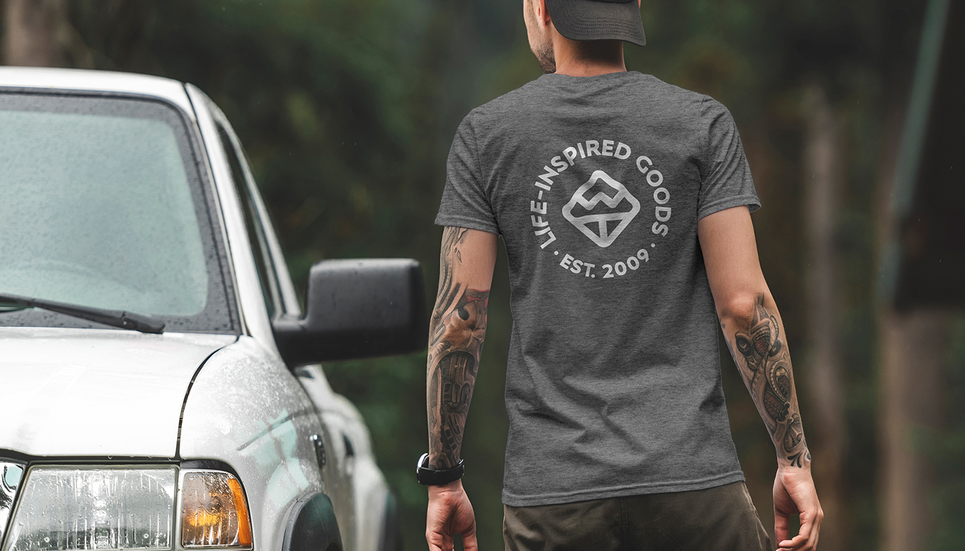 man wearing well told grey t-shirt back in forest logo design badge branding well told business card design home goods brand logo design wt letter logowell told etched water bottle flasks map glassware logo design branding visual identity by connor fowler cfowlerdesign